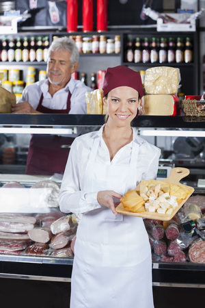 samples: Portrait of happy young saleswoman holding various cheese on cutting board with colleague in background at store Stock Photo