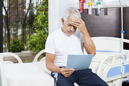 long depression: Tensed senior man reading reports while sitting on bed in rehab center