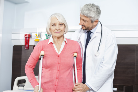 assisted: Portrait of senior female patient being assisted by mature doctor with crutches at rehab center