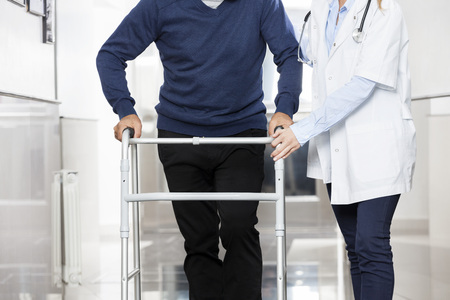 Midsection of female doctor assisting senior man with walker at rehab center