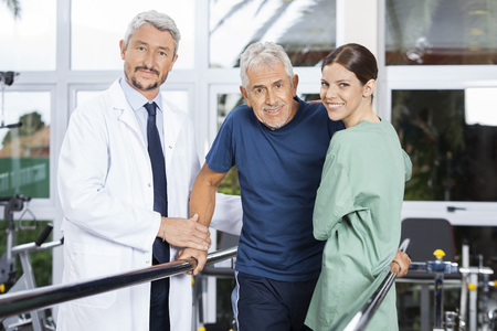 physiotherapists: Portrait of confident physiotherapists with senior patient in fitness studio at rehab center Stock Photo