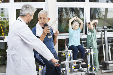 rehab: Senior man looking at doctor while drinking water in fitness studio of rehab center
