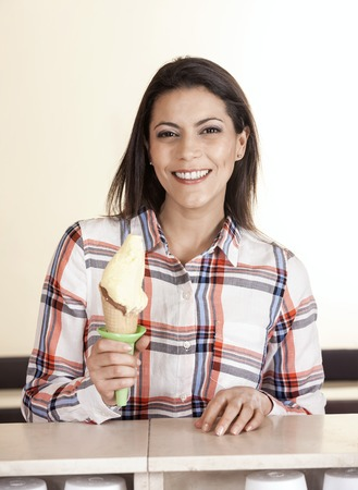 gelati: Portrait of smiling mid adult woman holding vanilla ice cream cone at counter in store Stock Photo