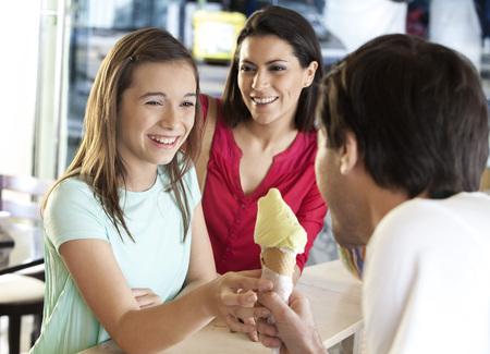 Madre feliz mirando la hija de la recepción de helado de vainilla de camarero en el salón Foto de archivo - 56707172