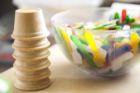 gelati: Closeup of ice cream cups by multicolored spoons in bowl at parlor