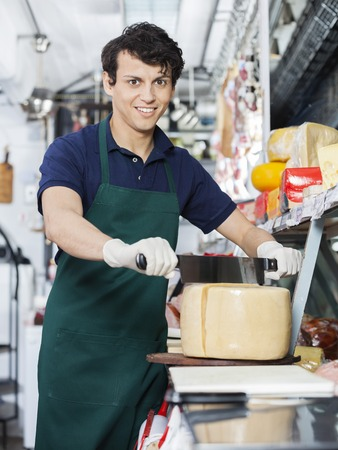 handled: Portrait of happy young salesman slicing whole cheese with double handled knife at counter in shop