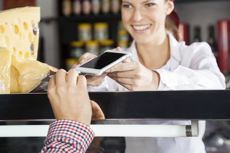 accepting: Happy saleswoman accepting payment from customer through credit card in cheese shop