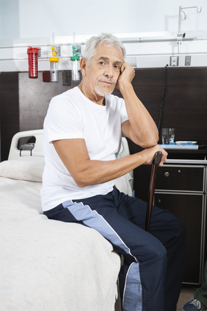 unhappy man: Portrait of sad senior man holding cane while sitting on bed at rehab center