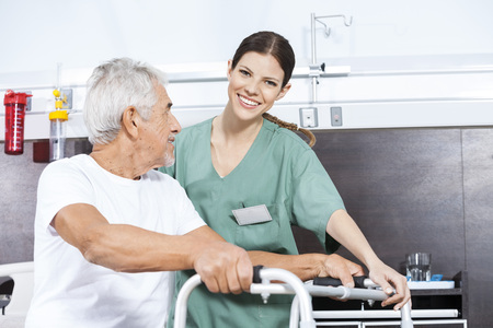 long term care services: Portrait of smiling female nurse assisting senior man to use walker at rehab center