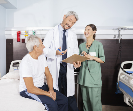 long term care services: Happy male doctor explaining report to senior patient while standing by nurse in rehab center Stock Photo