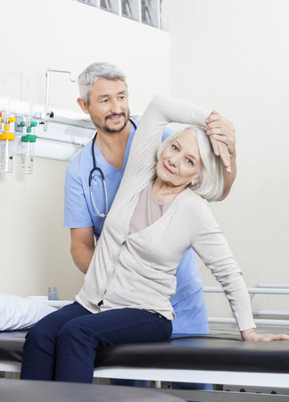 senior woman: Portrait of senior woman being assisted by mature physiotherapist with arm exercise in rehab center