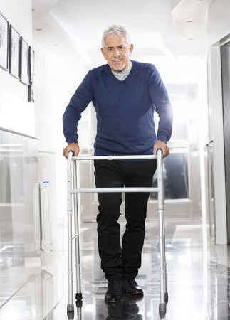 rehab: Portrait of smiling senior man using walker at rehab center