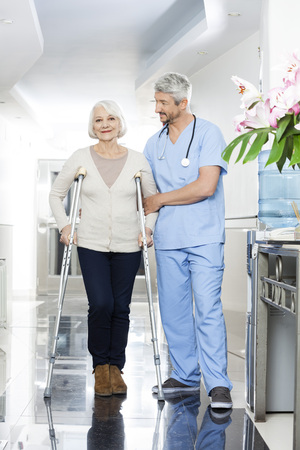 long term care services: Mature male physiotherapist helping senior woman with crutches in rehab center