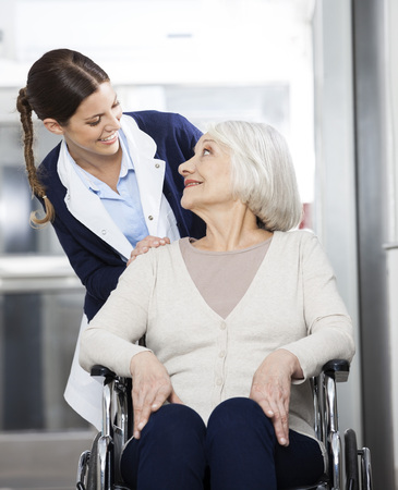 long term care services: Happy female physiotherapist looking at senior patient sitting in wheelchair in rehab center Stock Photo