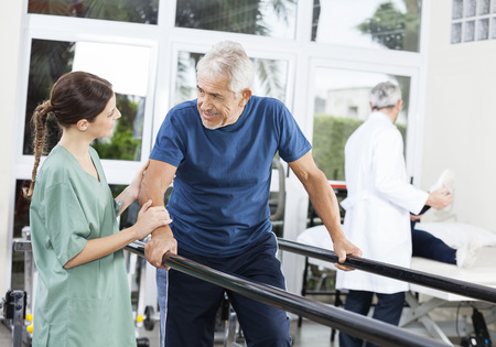 Senior patient looking at female physiotherapist while walking between parallel bars in rehab center