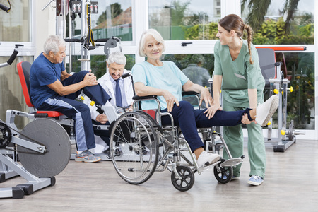 physiotherapists: Male and female physiotherapists guiding senior patients to exercise at rehab fitness center