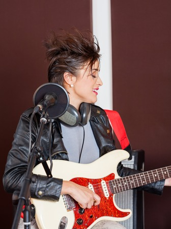 spiked hair: Funky female guitarist performing in recording studio Stock Photo