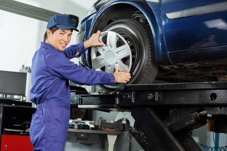 hubcap: Side view portrait of confident mechanic fixing hubcap to car tire at garage Stock Photo