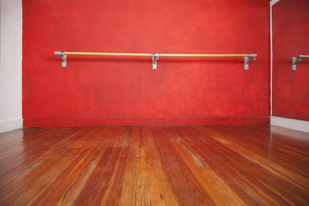 Ballet bar against red wall in empty dance studio