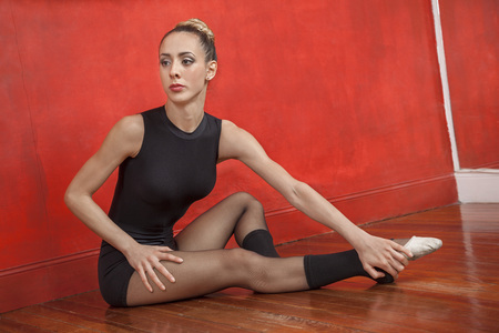 barre: Full length of young female ballet dancer stretching on the floor in dance studio