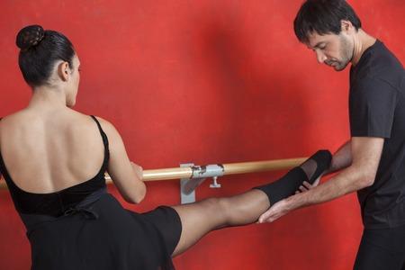 ballet hombres: Hombre entrenador ayudando bailarina de ballet femenino en barra contra la pared roja en el estudio