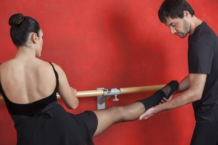 male ballet dancer: Male trainer assisting female ballet dancer at barre against red wall in studio Stock Photo