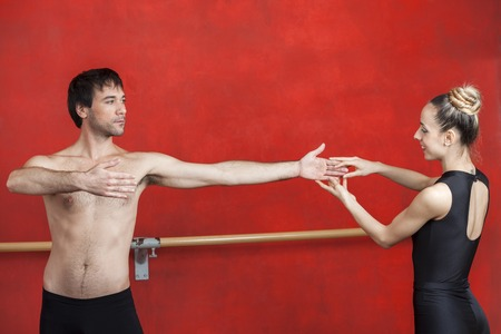 ballet hombres: Entrenador con el bailarín de ballet masculino practicando contra la pared roja en el estudio