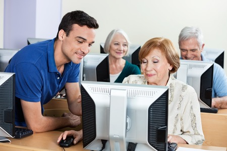 the elderly tutor: Male tutor assisting senior woman with classmates in background during computer class