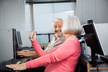 clenching: Happy senior woman clenching fist while looking at man in computer class