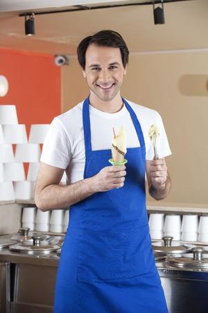 parlor: Portrait of happy waiter preparing ice cream at parlor Stock Photo