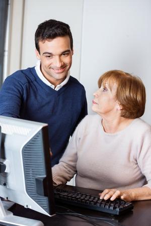 the elderly tutor: Happy male teacher assisting senior woman during computer class Stock Photo