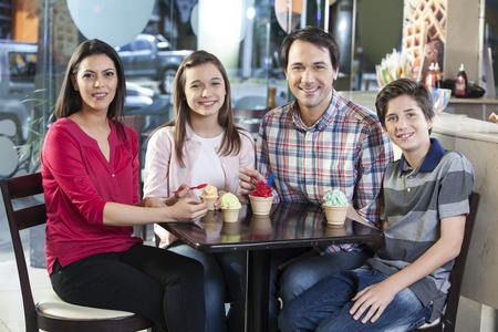 gelati: Portrait of smiling family with ice creams sitting at table in parlor