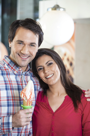 gelati: Portrait of smiling couple with vanilla ice cream at parlor