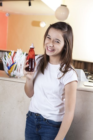 ice cream stand: Portrait of happy girl holding strawberry syrup in ice cream parlor Stock Photo