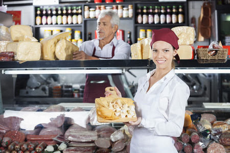 sample: Portrait of happy young woman holding various cheese on cutting board with colleague in background at store Stock Photo