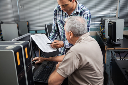 the elderly tutor: Male teacher showing clipboard to senior student in computer class