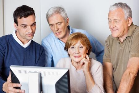Man tutor assisteren senior mensen in het gebruik van de computer in de klas
