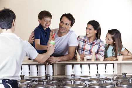 Happy family looking at boy while waiter serving him ice cream in parlor