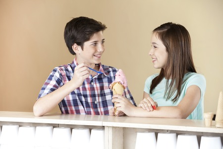 parlor: Smiling brother and sister having strawberry ice cream while looking at each other in parlor