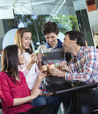 gelati: Happy family of four toasting ice creams at table in parlor