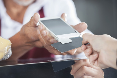 accepting: Cropped image of salesman accepting payment from customer through credit card in cheese shop
