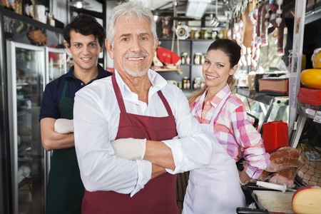 Portrait of confident salespeople in cheese shop