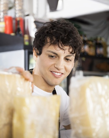 arranging: Young salesman arranging cheese in shop Stock Photo