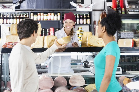 saleswoman: Smiling young saleswoman selling cheese to couple in grocery store Stock Photo