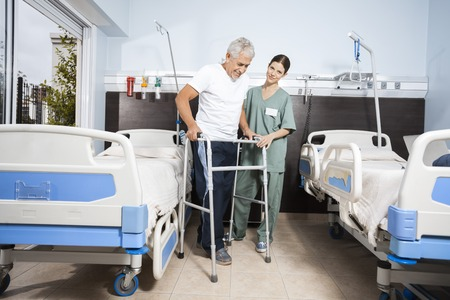 long term care services: Portrait of female nurse assisting senior patient in using walker at rehab center