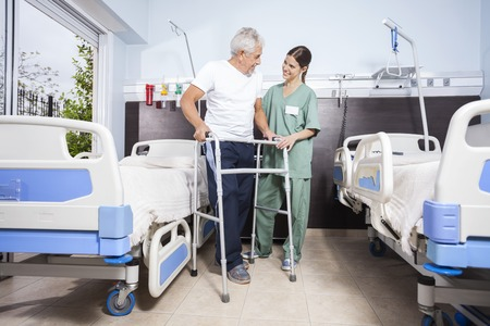 long term care services: Senior male patient using walker while looking at female nurse at rehab center Stock Photo