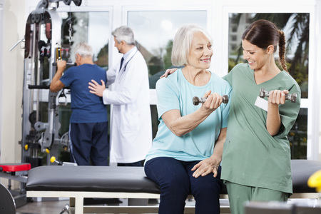 guiding: Smiling female nurse guiding senior woman exercising with dumbbell at rehab fitness center Stock Photo