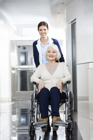 rehab: Portrait of female physiotherapist pushing senior woman in wheelchair at rehab center
