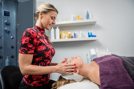 beauty parlor: Side view of beautician giving facial massage to mature woman in beauty parlor Stock Photo