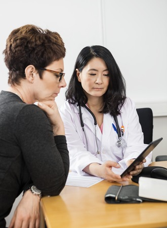 doctor appointment: Confident doctor showing digital tablet to female patient in clinic Stock Photo